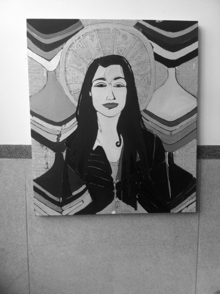 Greyscale. A painting of a woman with long dark hair, with what looks like a halo behind her head. There are structures that could be interpreted as pillars on either side of her.