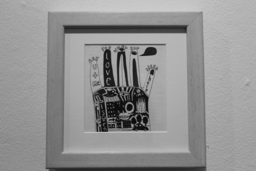"""Greyscale. A print of a hand in a grey frame. The hand has """"ask for what you need"""" written on top of the finger tips, and drawings of trees, an eye, tea, and buildings on the palm."""
