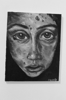 Greyscale. A painting of a woman's face. It is blotchy, and she is looking at the viewer with a sad expression.