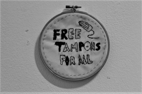"""Greyscale. An embroidery hoop with the words """"free tampons for all"""" stitched onto the cloth in all-caps. A tampon is embroidered into the right hand side of the cloth, and there is a stitched border."""