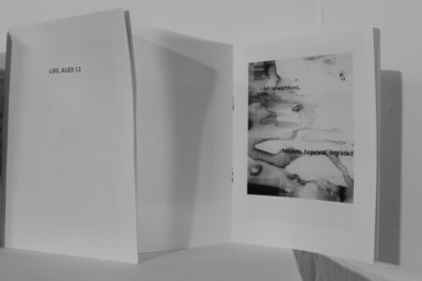 """Greyscale. A white booklet of which the front reads """"girl aged 12,"""" opened up. Another page has an abstract watercolour design with black text over it, which reads """"I feel so worthless, helpless, hopeless, degraded."""""""
