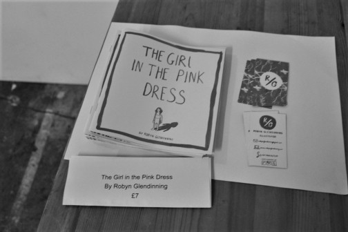 """Greyscale. A wooden table with Robyn Glendinning's business cards and her """"The Girl in the Pink Dress"""" zines, which are advertised as being £7"""