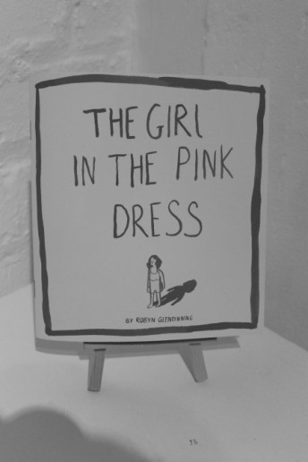 """Greyscale. A small card sign propped up in a wooden holder. The sign reads """"The Girl in The Pink Dress"""" at the top, underneath this is a drawing of a girl, with her shadow behind her. Underneath the drawing is """"by Robyn Glendinning."""""""