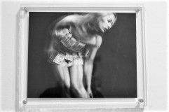 Greyscale. A photograph behind glass of a young white woman leaning down and to the right, with motion blur around her. She is wearing a small dress made of banknotes.