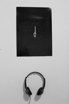 Greyscale. Black headphones hanging on the wall, below a black picture with small dots that look like stars, and the big dipper in the middle.