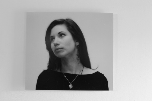 Greyscale. A white woman with dark hair looking up and to the left of the camera with an unreadable expression. She is wearing long earrings and a heartshaped necklace.