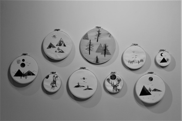 Greyscale. Nine pieces of art on cloth in embroidery hoops of different sizes. The art in these hoops all depict scenes of nature, such as mountains, trees, a rabbit, and a deer.