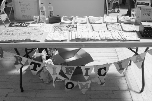 """A large table with an assortment of zines and badges on it. Hanging off the table is bunting that reads """"artificial womb"""" with a letter on every triangle."""