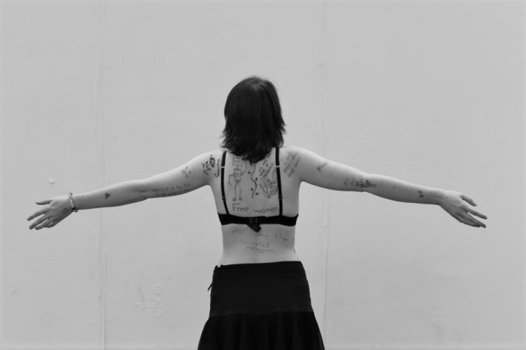 Greyscale. Ana Hine, a white woman, standing with her back to the camera and her arms out. There are a variety of drawings and phrases written onto her skin in pen.