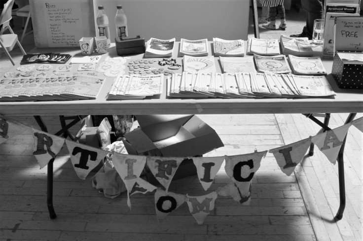 """Greyscale. A large table with an assortment of zines and badges on it. Hanging from the table is bunting that reads """"Artificial Womb"""" with a letter on every triangle."""