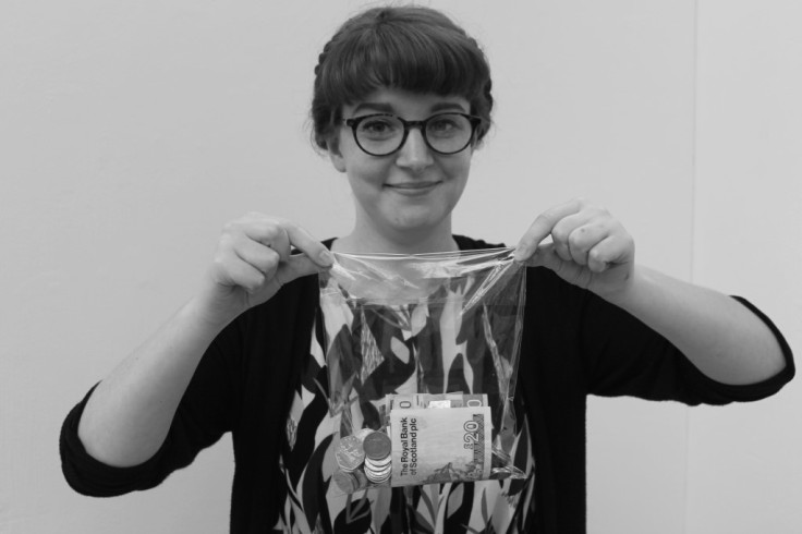 Beth, a white woman wearing glasses, holds up a bag of money. She is smiling.
