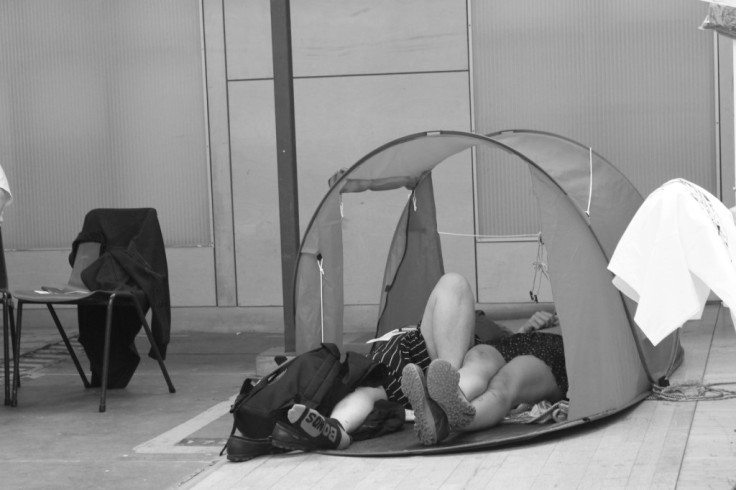 Two people lie side by side in a tent. The viewer can see their legs but not their faces.