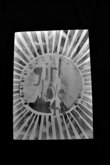 """Greyscale image. The front of the """"Girl Love"""" zine, issue #4. The centre image on the zine is shaped like a sun, with lots of rays pointing out."""