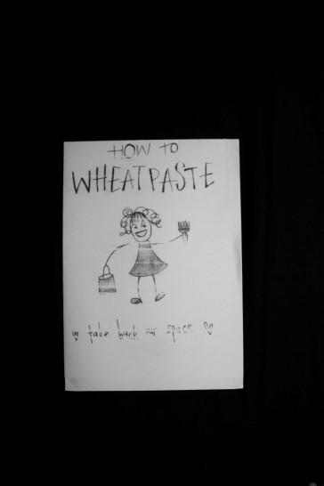 """Greyscale image. The """"How to Wheatpaste"""" mini zine. There is a drawing of a girl holding a paintbrush and a bucket of paint. Under this drawing are the words """"take back our space"""" surrounded by two hearts on either side."""
