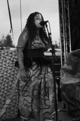 Chantal Brown, a black woman with long wavy dark hair, singing into a floor mic.
