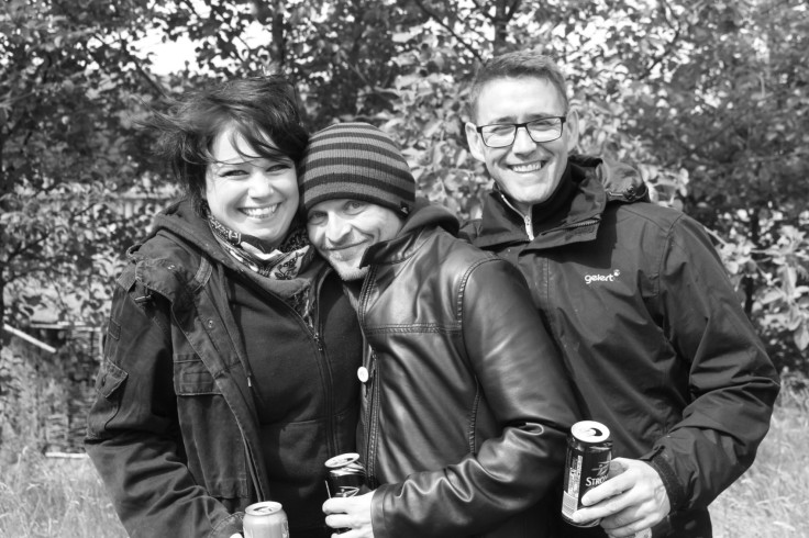 Greyscale. A white woman and two white men standing next to each other in front of trees. They are looking at the camera, smiling, and holding beer.