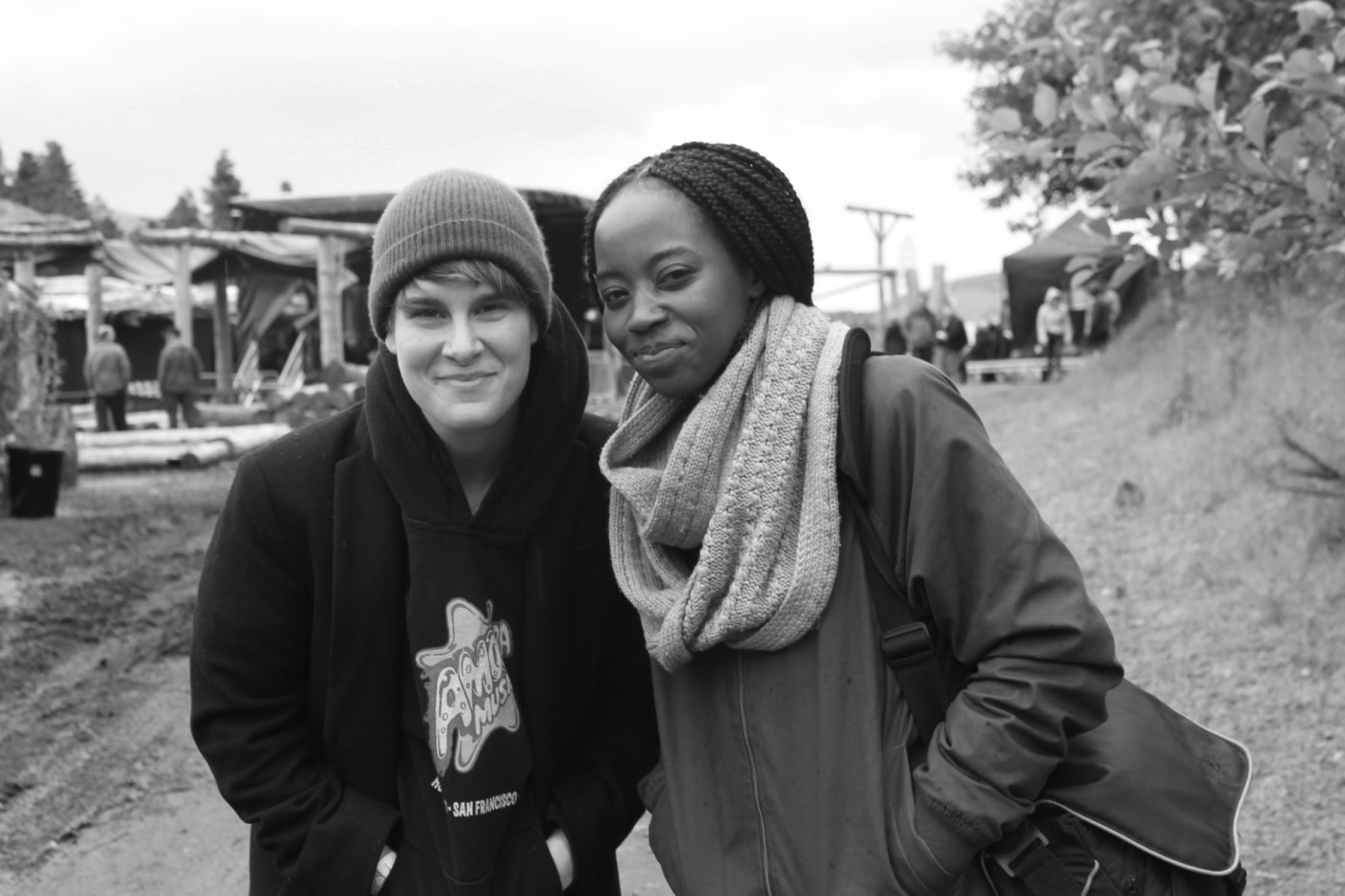 Greyscale. A butch white woman (Sofia B) standing next to a black woman with long braided hair. They are both smiling.