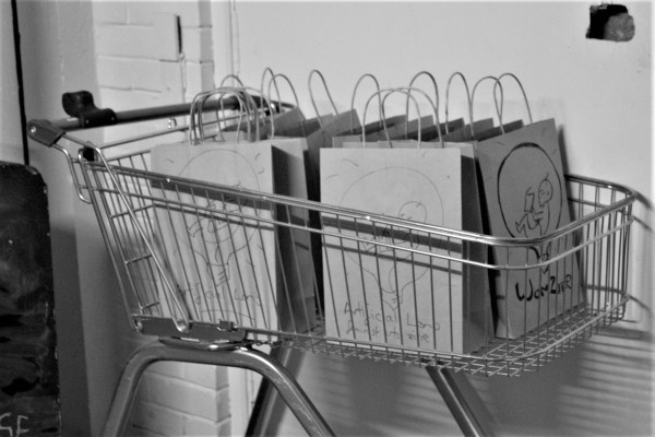 """Greyscale. A shopping trolley with lots of small paper bags inside it. The bags say """"Artificial Womb Feminist Arts Zine"""" and have a picture of a baby in a lightbulb reading a book."""