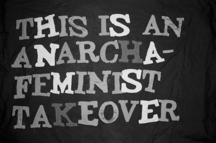 """Greyscale. A large piece of cloth with cloth capital letters sewn onto it, reading """"this is an anarcha-feminist takeover."""""""