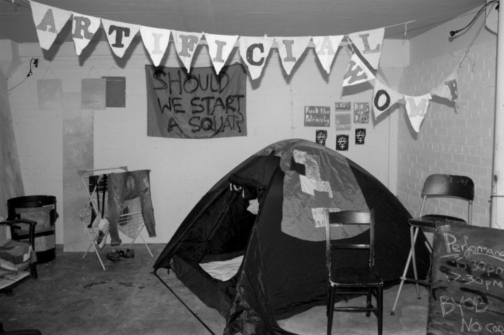 """Greyscale. A shot of a room in which there is a small tent. There is a sign on the wall that reads """"Should we start a squat?"""" two chairs, an assortment of feminist signs on the wall that read """"fuck the patriarchy,"""" """"riots not diets,"""" """"feminist,"""" and the anarcha-feminist symbol. There is bunting hanging from the ceiling that reads """"artificial womb"""" with a letter on each triangle. A stand-up sign reads """"performance 6:30/7:30pm BYOB."""""""