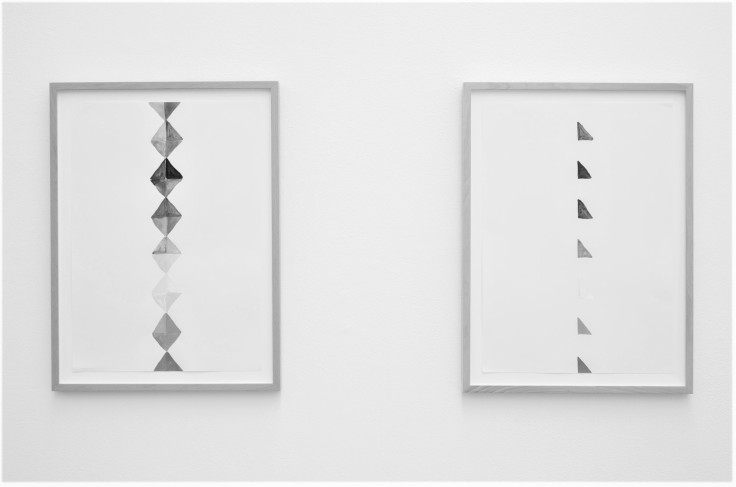 Greyscale. Two rectangular framed paintings on a white wall. The first painting is of small differently-shaded diamond-shapes in a vertical line. The second is of right-angled triangles spaced out, in a vertical line.