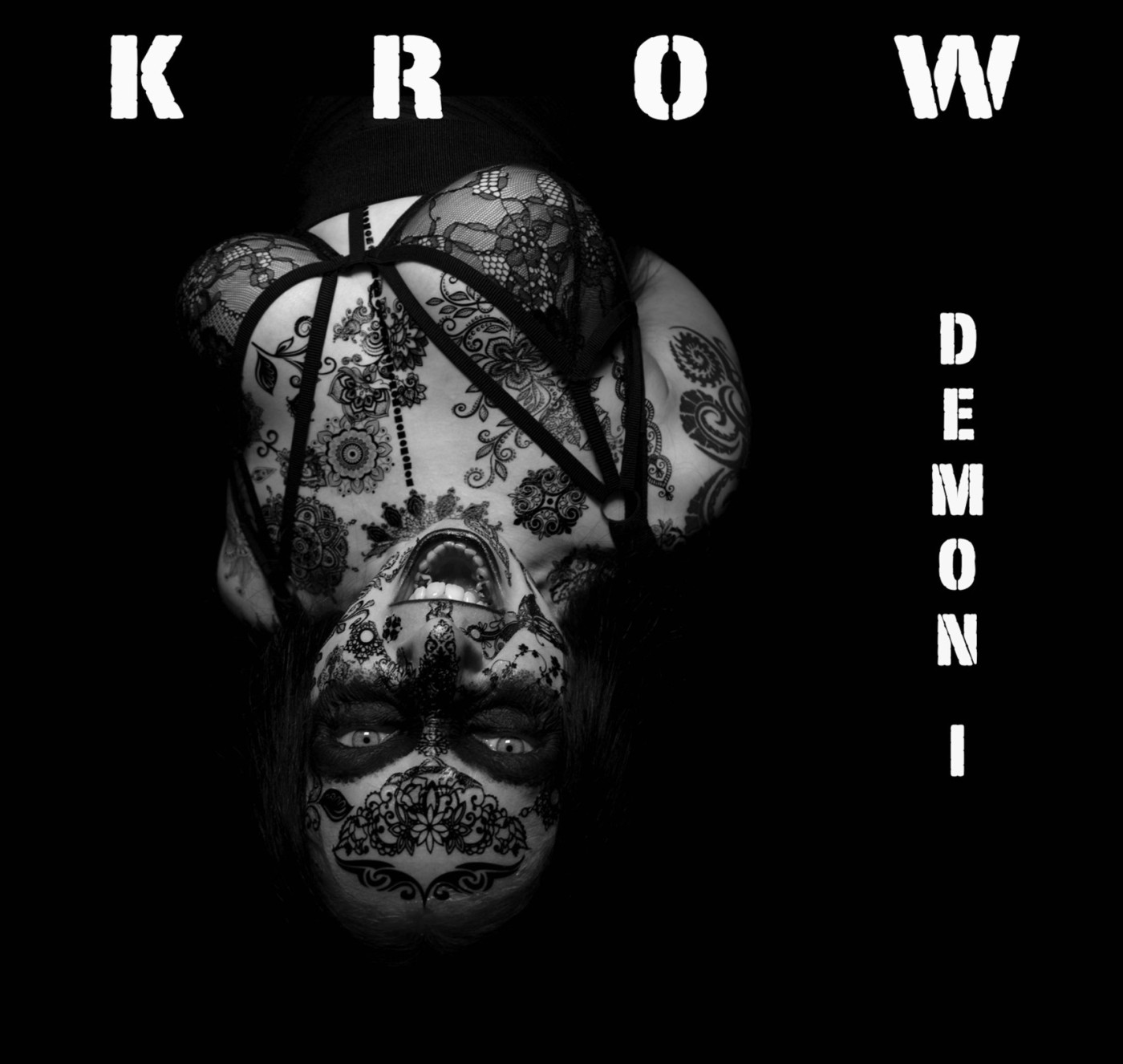 "Greyscale. The album cover of KROW's ""Demon, I."" The word ""KROW"" is stamped in white letters on top of the black background, and ""Demon I"" is down the right-hand side. KROW, a heavily-tattoed white woman, is in the middle of the image, lying upside-down with her mouth open. The image has a powerful energy."