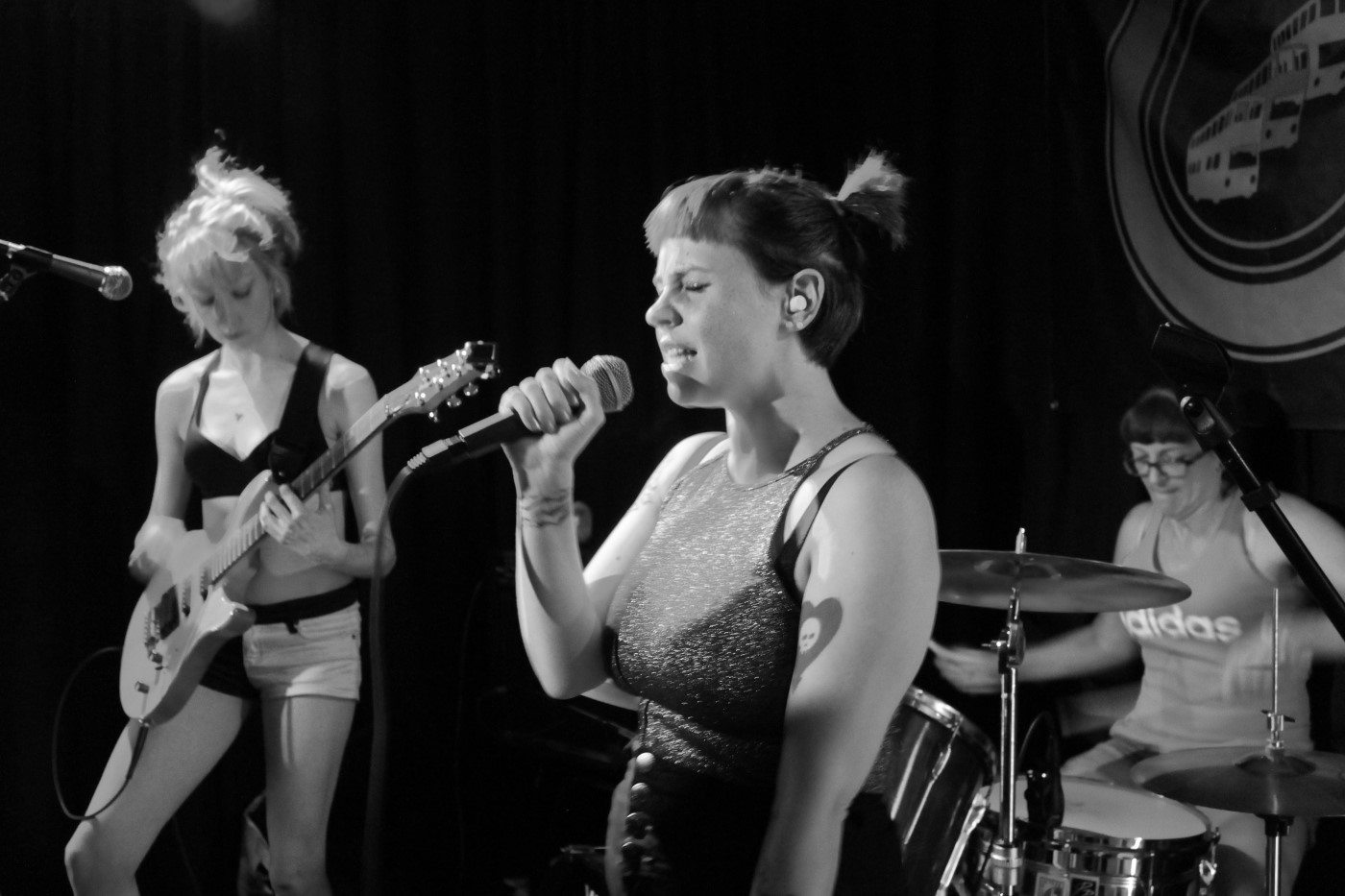 Greyscale. A white woman with dark hair holds a microphone in one hand and sings with her eyes tightly shut. To her left is a white woman with blonde hair, who looks down at the bass guitar she's playing. Behind them is a white woman with dark hair who's playing drums.