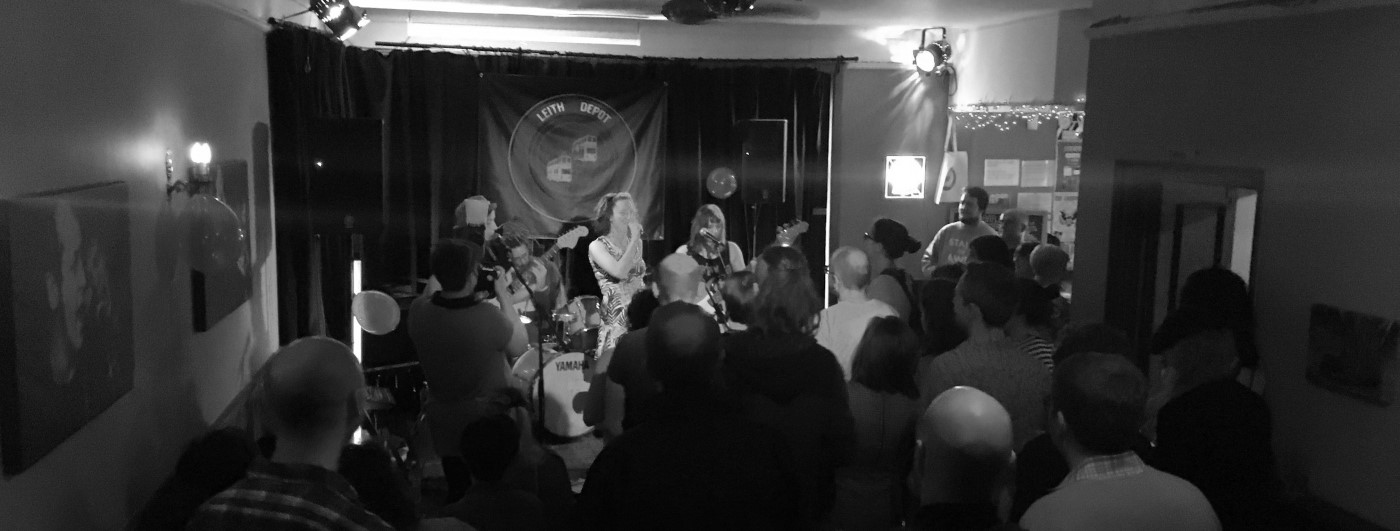 """Greyscale. A shot from behind and above a crowd, in front of which there are three women playing guitars and singing into floor mics. There is a stage light on the right of the ceiling, shining towards the performers. Behind them is a cloth sign pinned up that reads """"Leith Depot"""" and there is a picture of buses beneath the words."""