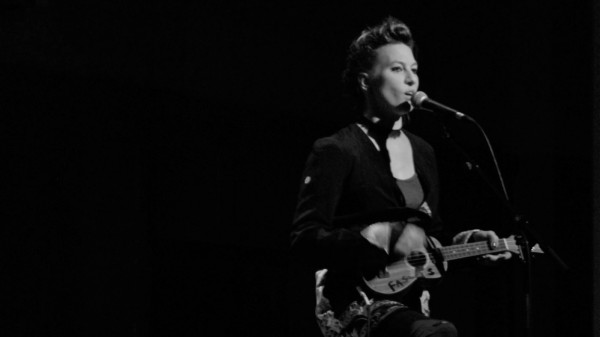 A greyscale image of Amanda Palmer, a white woman, playing a ukelele and singing into a floor mic. She is wearing a black jacket.