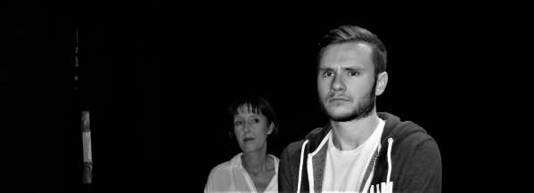 A greyscale image of a young white man looking into middle distance as if he is about to cry. A w woman stands behind him to his left, looking at him with an unreadable expression.