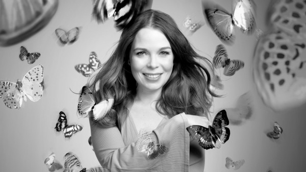 A greyscale image of Juliette Burton, a white woman with dark hair. She is surrounded by large butterflies, smiling and looking at the viewer.