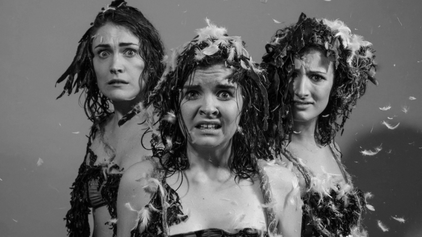 A greyscale image of three white women who all have damp hair and are covered in small white feathers. They look distressed and are all looking towards the camera.
