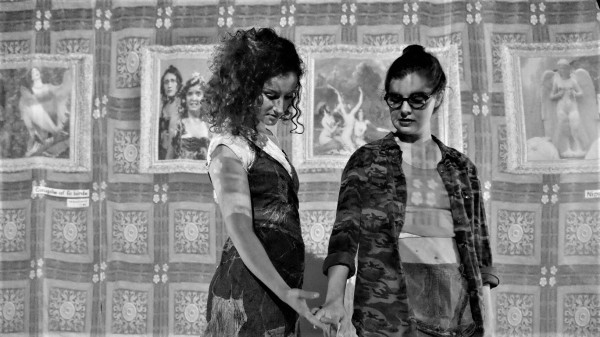 A greyscale image of two white women, one wearing glasses in front of various pictures that are attached to a cloth background. The women are holding hands and looking at their interlocked fingers.