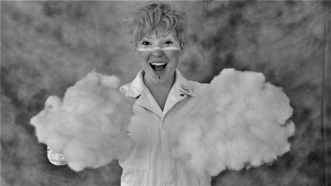 Kimber Hall, a white non-binary person looking at the camera with a joyous expression. They are wearing a white shirt and are holding large fluffy cloudlike objects.