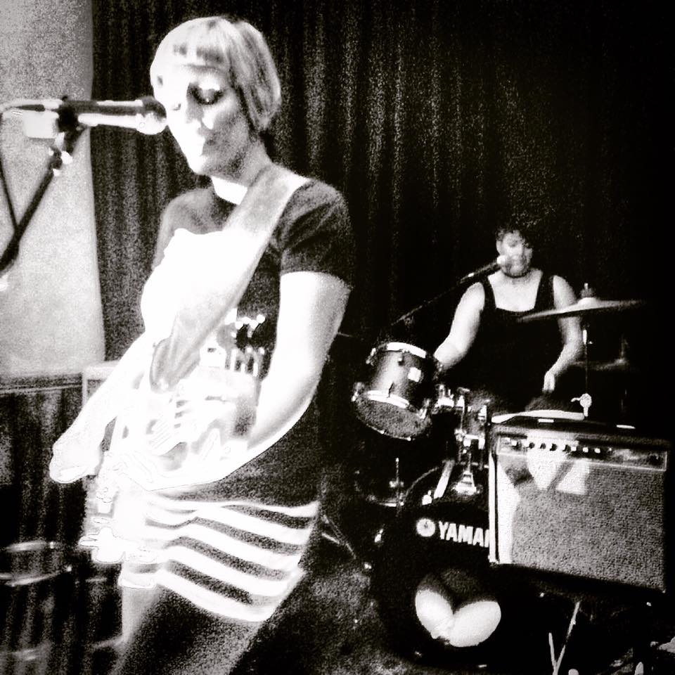 A low-res greyscale image. Bassist and lead singer Jo D'arc, a white woman with short blonde hair, sings into a floor mic and plays bass. Behind her, Nicky D'arc, a white woman with dark hair, plays drums.