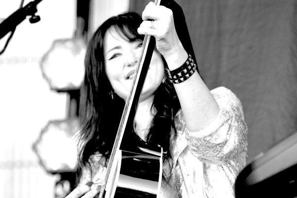 Greyscale image. KT Tunstall, a woman of Chinese, Scottish, and Irish heritage with long dark hair, playing an acoustic guitar and smiling.