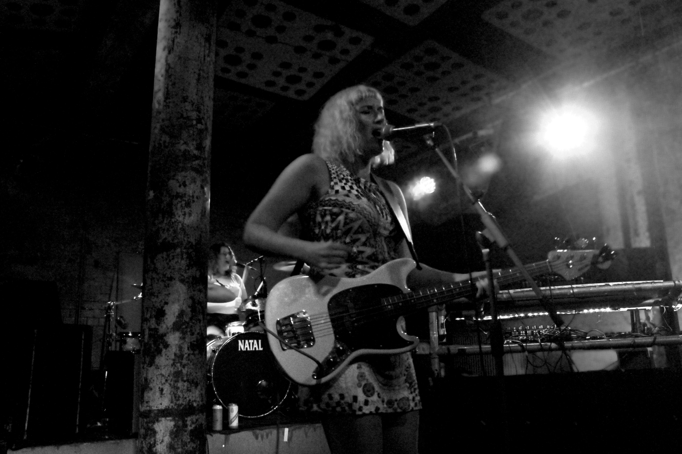 Greyscale image, The Twistettes. Jo D'arc, a white woman with blonde hair, playing a bass guitar, singing into a floor microphone. Behind her. Nicky D'arc, also a white woman, is playing drums.