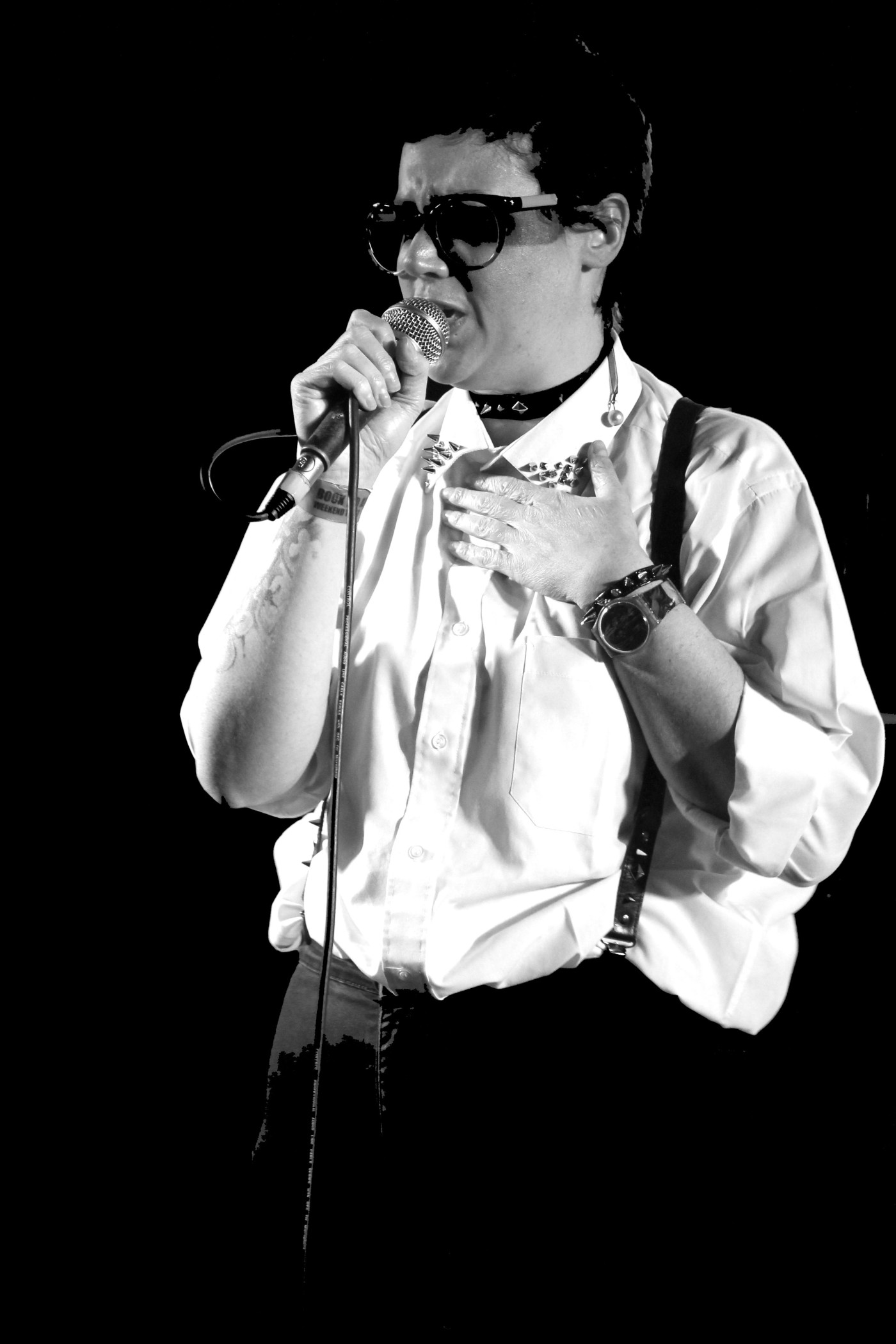 [Greyscale image] Meg Stewart, singing into a floor mic held in her right hand, with her left hand on her heart.