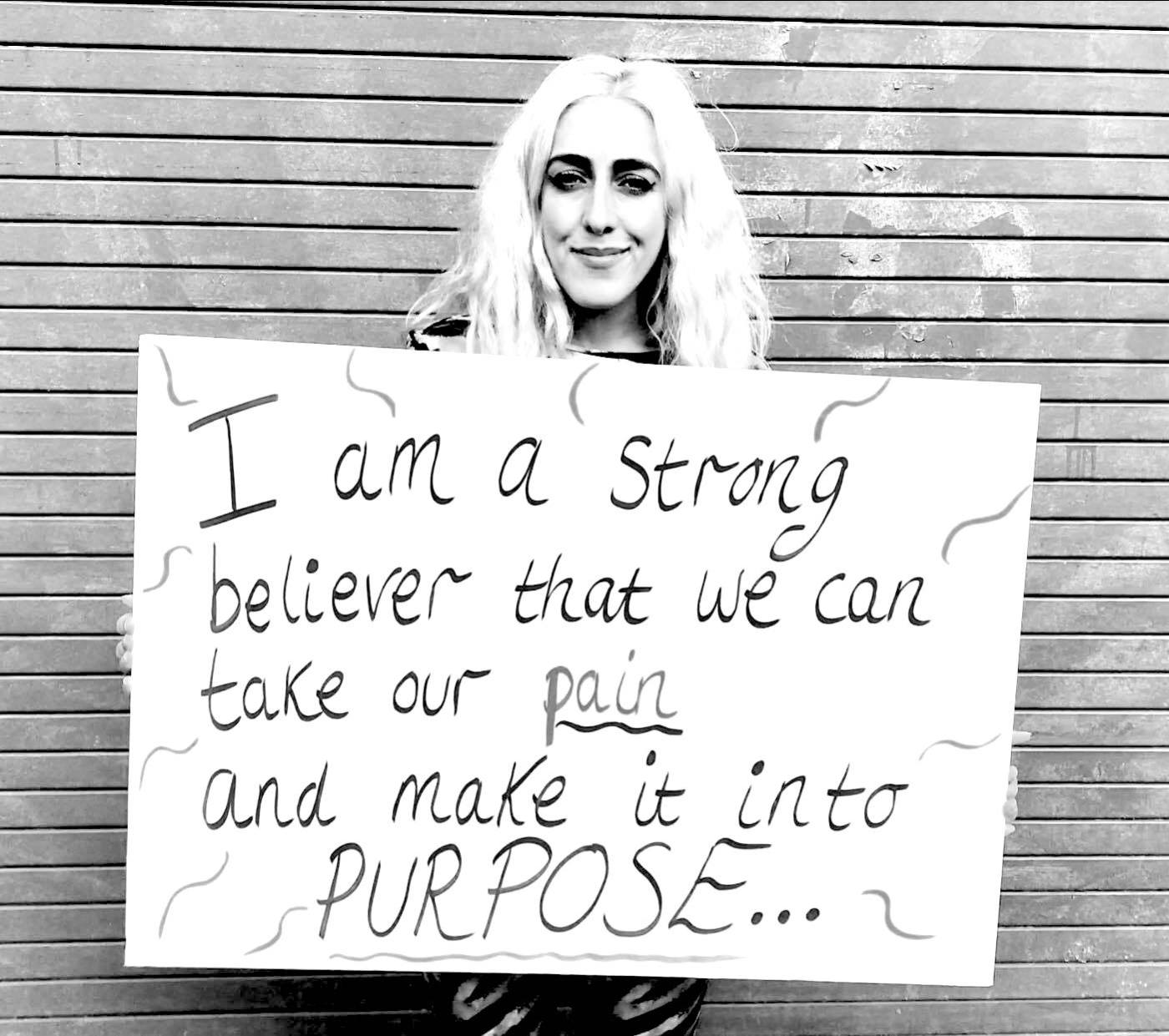 """A greyscale image of Miranda Arieh, a white woman, holding a sign that reads """"I am a strong believer that we can take our pain and make it into purpose."""""""