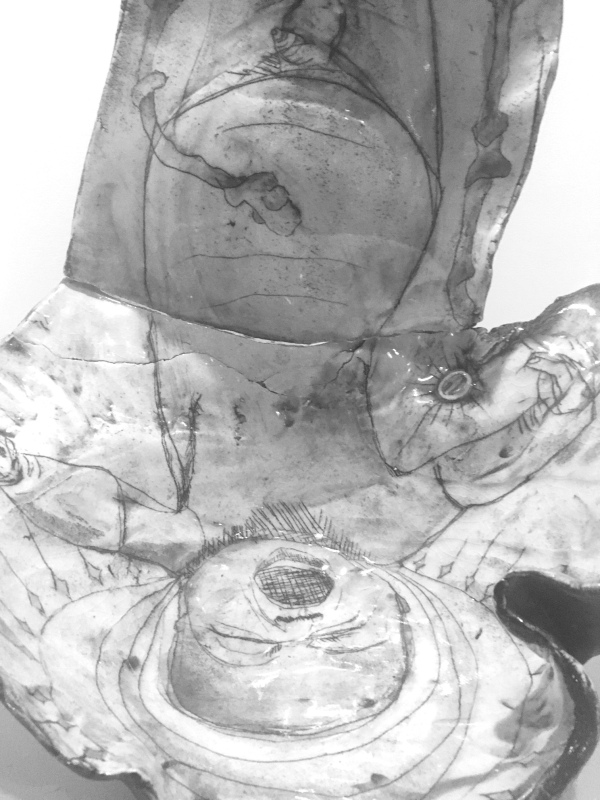 Greyscale. An upside-down crying newborn baby Jesus is painted onto a thin piece of pottery. Its eyes are screwed shut and its mouth is wide open. The pottery follows the shape of the baby and bends above the umbilical chord.