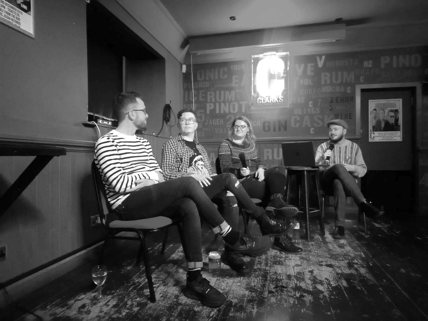 A greyscale image of four people sitting in Clarkes Bar. One has a laptop in front of them and is holding a microphone.
