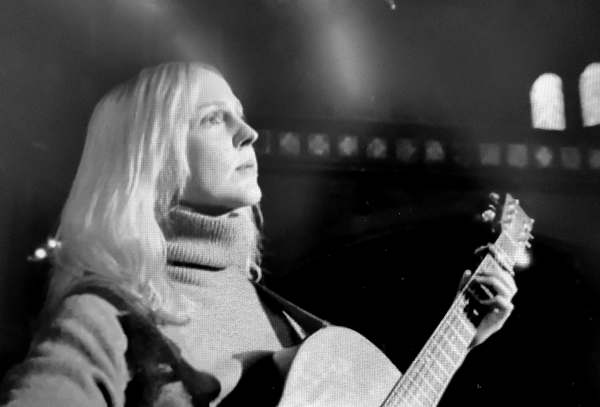 Image is Greyscale. Laura Marling stands alone on stage, white-blonde hair falling around her face, wearing a comfortable looking grey jumper. She performs with only an acoustic guitar, and gazes off into the middle distance.