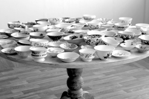 Greyscale. A circular wooden table with a large assortment of china bowls on it.