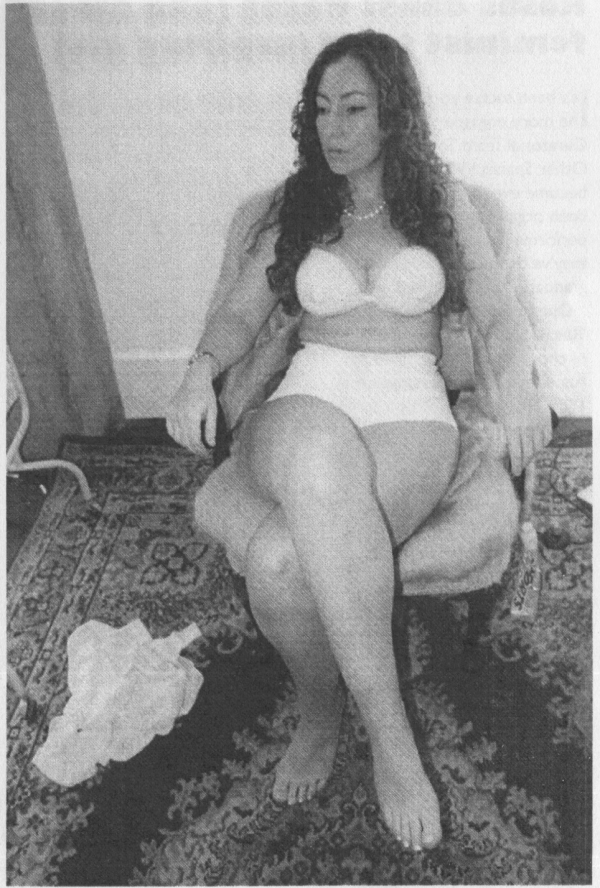 Greyscale. Private V Public sitting in a soft chair in her living room, wearing a white bra and underpants.