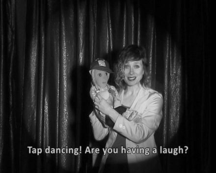 "Greyscale. A woman holding a puppet, standing against a stage curtain. Text at the bottom of the image reads ""Tap dancing! Are you having a laugh?"""