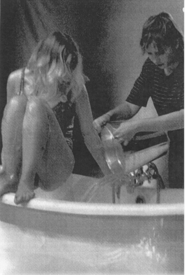 Greyscale. A woman crouched on the edge of a bath as someone pours water into it.