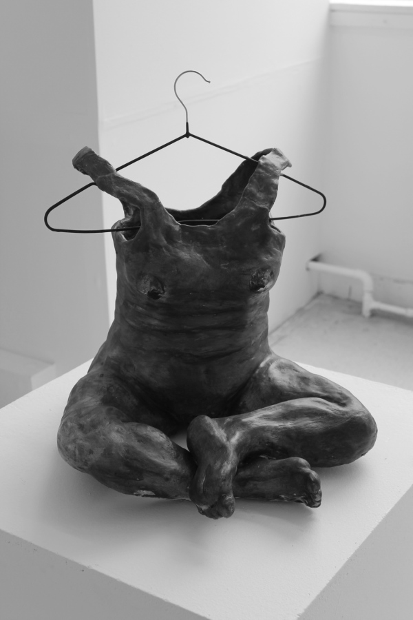 Greyscale. A sculpture of a woman's body, minus the head. The woman's shoulders turn into the straps of a dress, and these straps are hung on a metal hanger. The woman