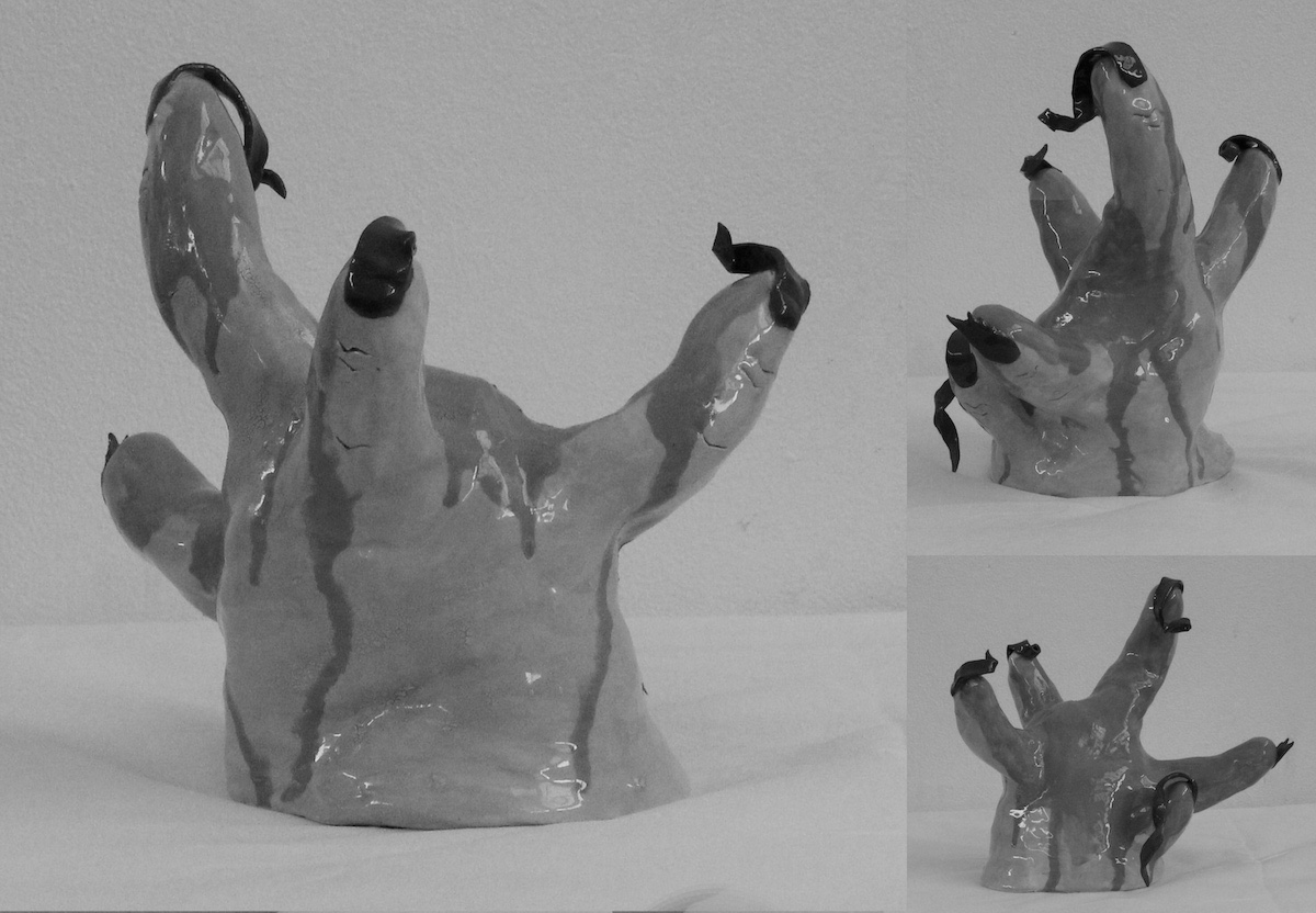 Greyscale. Ceramic hands emerge from the ground, covered in blood, with gnarled fingernails. The proportions are all wrong, fingers coming out at any angle. They're disturbing.