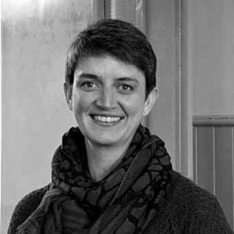 Greyscale. Maggie Chapman, a white woman with dark hair in a pixie cut, wearing a scarf, looking at the camera. She is smiling.