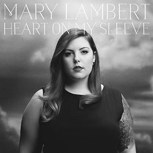 Greyscale. The album cover for Heart on my Sleeve. It features Mary Lambert, a white woman with dark hair, looking towards the viewer. She is standing in front of an overcast cloudy background.